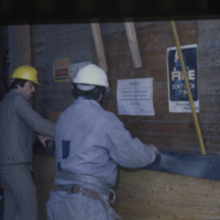[Two men in hard hats moving plywood]