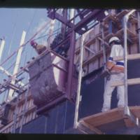 [Two men in hard hats building a grain elevator]
