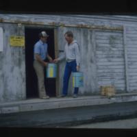 [Two men loading blue buckets of POOL brand Amine]