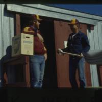 [Two men in front of storeroom]