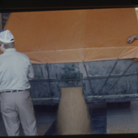 [Three men watching grain pour from truck to grain elevator]