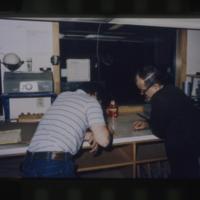 [Two men sorting or counting grain]