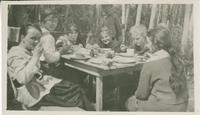 [Six women eating around a table at a camp]