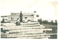 [Three women and a man standing on pile of logs]