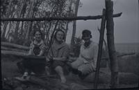 [Three women sitting on a log by campfire]