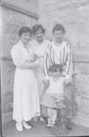 [Three women and a little girl by a stone building]