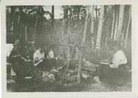 [Women eating meal around fire]