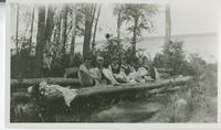 [Six women in swimsuits sitting on a log]